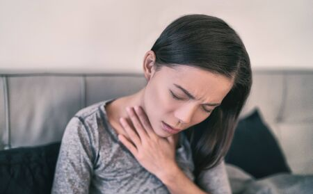 COVID-19 Corona virus symptoms are pneumonia, shortness of breath, chest pain, body aches or breathing difficulties. Asian woman sick of Coronavirus at home. Banco de Imagens