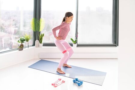 Resistance band fitness home workout woman doing squats exercises using loop bands for leg glutes standing exercise with strap elastic. Glute muscle activation for thighs cellulite. Stock Photo