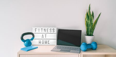 Fitness at home online exercise class on computer laptop with training weights and resistance band. Coronavirus COVID-19 Social distancing sign lightbox banner staying indoor while gyms are closed.