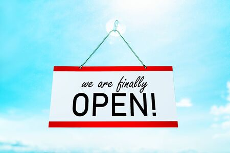 COVID-19 WERE FINALLY OPEN ! sign hanging on window store end of confinement stores reopening . Retail businesses opening again for non essential services. Sunny summer background.