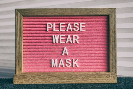 COVID-19 sign PLEASE WEAR A MASK at grocery store entrance for coronavirus prevention. Message on pink felt letter board. Compulsory measure in businesses for face protection wearing. Stock fotó