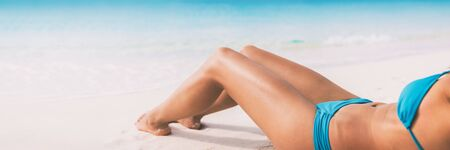 Summer beach bikini body woman lying on white sand sun tanning smooth legs sun tan for laser hair removal concept banner panoramic background.