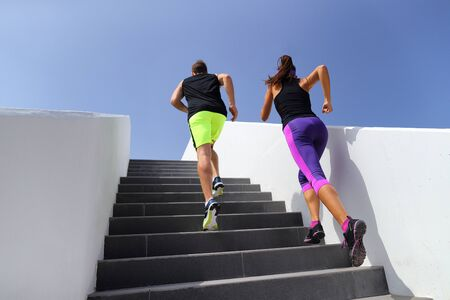 Couple running up stairs at fitness gym. Healthy active lifestyle sport people exercising cardio climbing staircase in city.