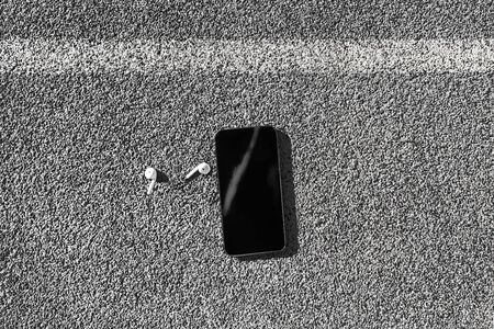 Wireless wearable technology in ear earbuds with mobile phone top view on urban city street background texture. Black screen on smartphone.