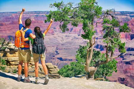 Grand Canyon hikers tourists couple cheering success with arms up happy for hike achievement. Backpackers hiking with backpacks standing at view of famous american landmark, USA trip travel. 版權商用圖片