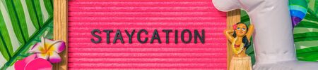 Staycation banner sign for summer vacation plans during COVID-19. Funny pink felt board text for staying home for the holidays. What to do this summer without traveling.