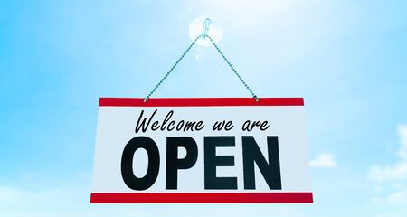 COVID-19 Open business sign saying Welcome we are OPEN hanging on window storefront reopening Retail businesses opening again. Sun blue sky summer background. end of confinement.