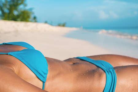 Sexy bikini model lying down on beach tanning suntan skincare body closeup of woman stomach wearing blue fashion swimwear.