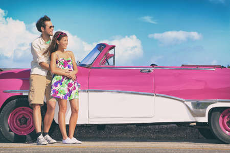 Couple driving pink vintage car on summer road trip travel fun.. Happy smiling young couple during summer road trip travel in Havana, Cuba. Interracial couple, Asian woman, Caucasian man. Stockfoto