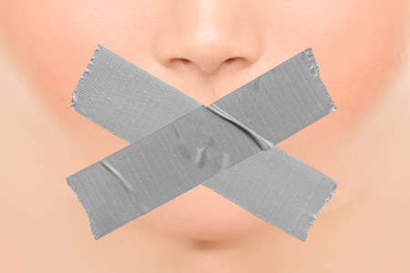 Woman silenced with adhesive duct tape covering closed mouth. Censorship, shut down of freedom of speech. Face nose and lips. Archivio Fotografico - 150760060