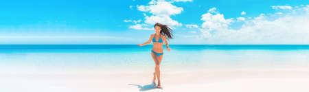 Beach Asian woman with fit summer bikini body happy running enjoying Caribbean vacation laughing of joy in tropical destination banner panorama. Blue swimwear model enjoying summer holidays. Standard-Bild