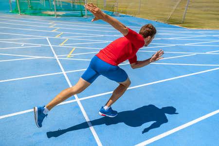 Runner athlete starting running at start of run track on blue running tracks at outdoor athletics and field stadium. Sprinter on race. Sport and fitness man sprinting.