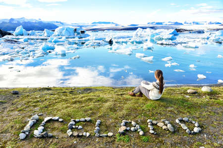 Iceland nature landscape Jokulsarlon glacial lagoon - ICELAND text written with rocks. Woman enjoying view visiting tourist destination landmark attraction glacier lake, Iconic Vatnajokull.