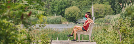 Mask wearing woman sitting relaxing on bench outside in summer nature park for coronavirus prevention. Protectve face covering COVID-19 lifestyle. Banner panoramic.
