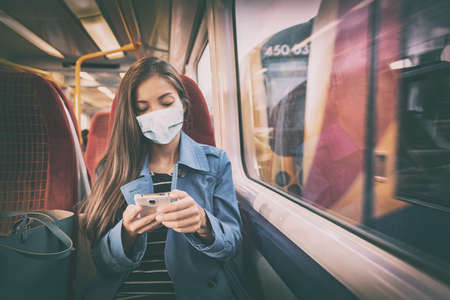 Mask wearing mandatory inside public spaces for transport such as train station and bus. Asian woman passenger using mobile phone with face covering wear sitting indoors on commute. Stock Photo
