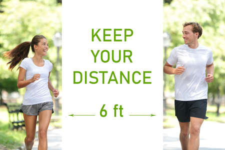 KEEP YOUR DISTANCE 6 feet prevention sign Covid-19 social distancing for people walking in city park talking together during walk run jogging. Asian woman jogger running with man.