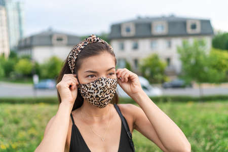 Asian woman putting on COVID-19 face mask wearing leopard fabric pattern masks matching fashion outfit outside in city for coronavirus. Summer lifestyle outdoor. Corona virus.