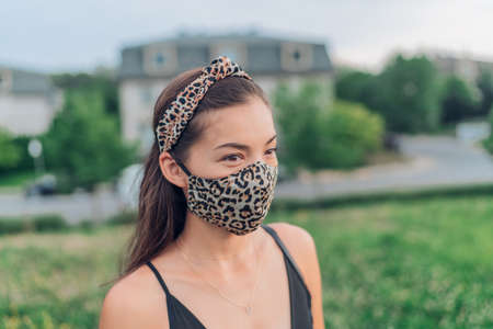 COVID-19 mask wearing Asian girl leopard fabric handmade masks mandatory in city. woman walking with face mask protection as coronavirus prevention in city park summer lifestyle outdoor. Corona virus.
