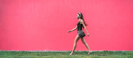 COVID-19 mask wear in city girl walking wearing mask as coronavirus prevention outside in city against street pink wall banner background. Corona virus new lifestyle.