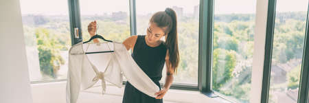 Buying new clothes Asian woman happy looking at purchase of fashion white top from clothing store panoramic banner.
