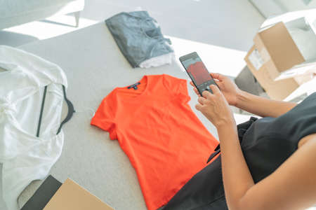 Selling online through phone app taking mobile photo of t shirt doing e-commerce small business at home.