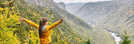 Happy hike travel woman with open arms outstretched in happiness carefree enjoying fall autumn panoramic banner background.