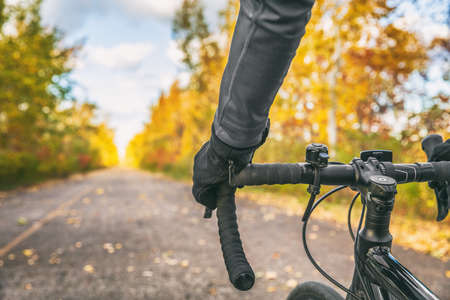 Biking first person view of bike cyclist POV showing hands and handlebar on road bicycle riding on outdoor commute in autumn nature.
