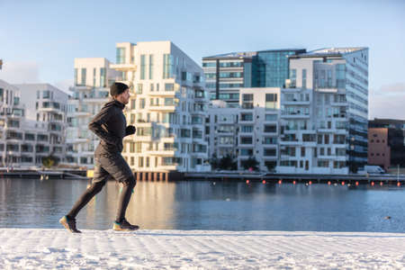 Winter run city lifestyle runner athlete man jogging outside on modern urban harbour street waterfront. Running active living healthy people. Stock Photo