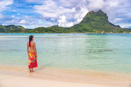 French polynesia tropical beach vacation backgrround. Bora bora island famous destination woman in Tahiti wearing polynesian skirt bathing in turquoise ocean. Paradise holiday.