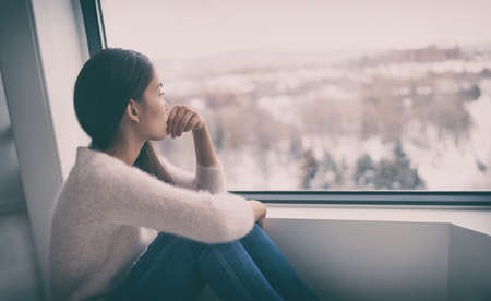 Depression, mental health, psychology therapy - mind wellness well being Asian girl with winter blues seasonal affective disorder feeling sad or heart broken with breakup alone. Loneliness, burnout , despair.