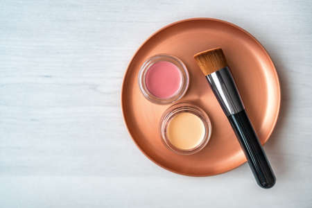 Make-up beauty products cream blush and concealer jars on mixing palette with brush for makeup artist. Top view background. Stock Photo