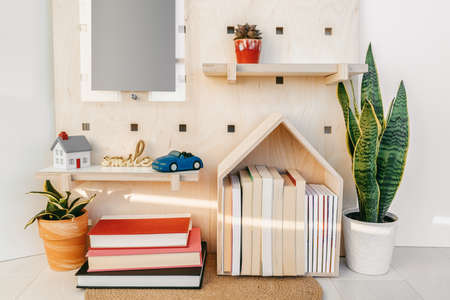 Home decor cozy wall shelves with books and toy car. New house decoration concept. Plants, wooden shelf, happy sign. Фото со стока