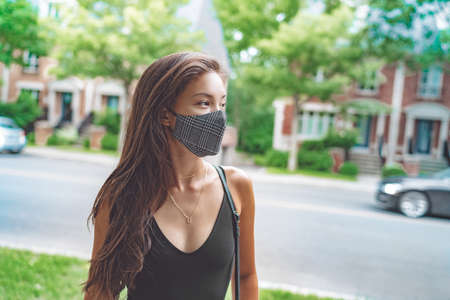 Asian woman walking in city street wearing face mask for COVID 19 prevention. Happy young student with fashion pattern cloth mouth covering outside. Corona virus concept.