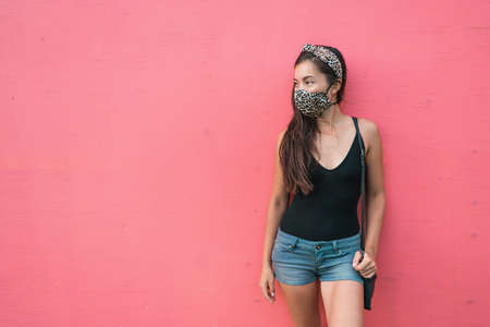 Mask wearing is mandatory in indoor spaces and public park for COVID 19. Asian woman is using face mask with fashion leopard fabric on pink wall background. City lifestyle outside for corona virus.