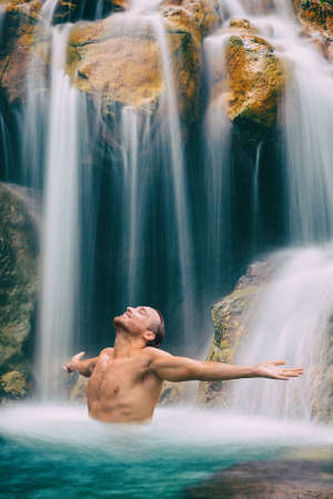 Hawaii waterfall happy man freedom with open arms. Carefree relaxing male adult under fresh natural water in nature forest. Wellness and spa.