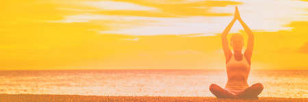 Yoga meditation banner background woman meditating on sunset beach sky with copy space panoramic. Фото со стока
