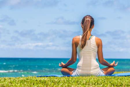 Yoga meditation woman meditating in lotus pose on exercise mat on beach grass. Фото со стока