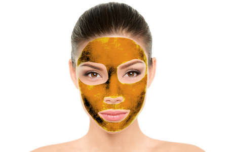 Gold mask luxury facial treatment for Asian women. Chinese beauty woman putting 24k real gold on skin for cleansing pores and nourish, skincare. Wellness spa concept.