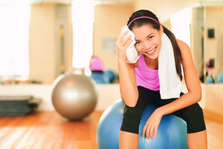 Asian fitness girl training at gym wiping sweat with towel post workout happy at gym. Exercise and healthy living weight loss concept.