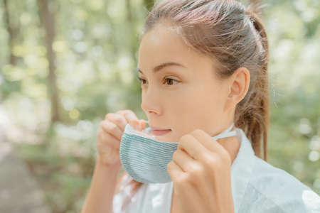 Asian beauty woman putting on mask on face. Wearing corona virus prevention masks for long hours are creating irritation, skin problems, acne pimples.