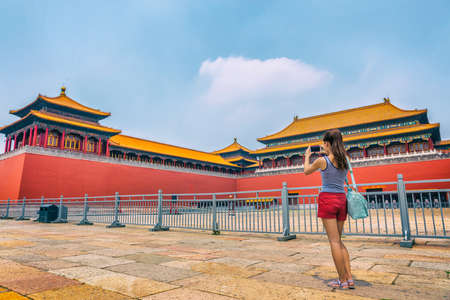 Woman taking mobile phone picture of Beijing tourist attraction, imperial architecture landmark. Asia travel, tourism destination popular attraction. Chinese girl. Stock Photo