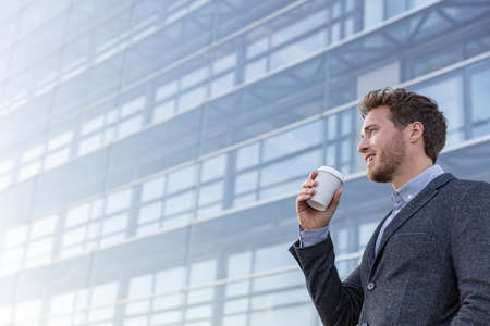 Happy young business professional man drinking coffee cup on his morning commute walk to work. Caucasian businessman with hot drink on office background looking away with satisfaction.