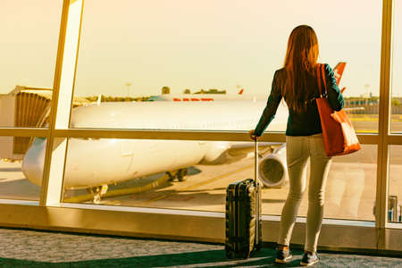 Airport travel woman looking through window sunset at airplanes on tarmac waiting for flight departure leaving for business trip holiday at first class lounge terminal delayed boarding.