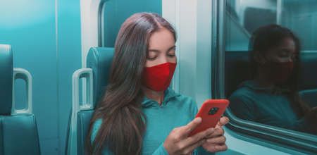 Face mask in public transport like train, bus. Woman passenger using mobile phone with face covering on subway commute ride at night.