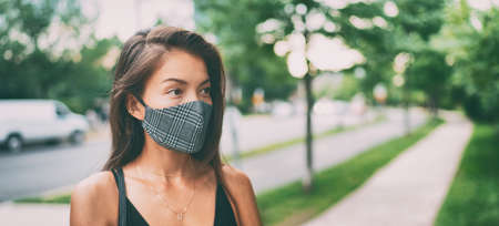 Asian woman walking outside wearing stylish fashion cloth face mask in plaid pattern. Serious young ethnic model portrait banner panorama. Stock fotó