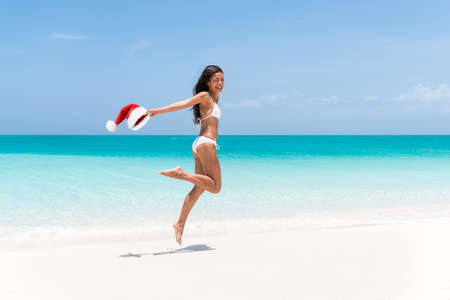 Christmas holiday at the Caribbean beach. Happy funny woman jumping of joy for weight loss or laser treatment with Santa Claus hat. Paradise winter vacation in the south, bikini body girl.