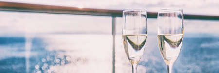 Two champagne glasses or sparkling white wine flutes on ocean landscape background, panorama banner for luxury travel vacation. Drinks in sun on couple cruise holiday. Standard-Bild