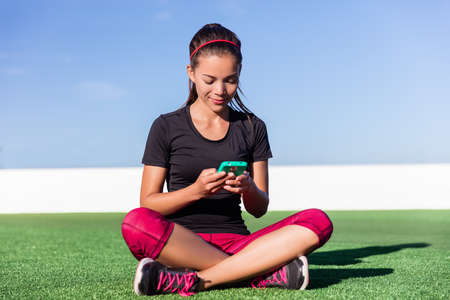 Active healthy lifestyle fitness smartphone app tracking weight loss progress or exercise goal. Happy Asian sporty woman using mobile phone for sms message texting during outdoor summer workout. 免版税图像