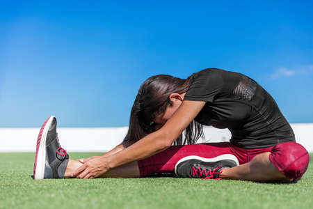 Fitness woman stretching back and leg muscles with toe-touch stretches. Sporty young athlete doing a one leg seated forward bend yoga stretch on outdoor grass. Sitting head to knee fold over pose. 免版税图像