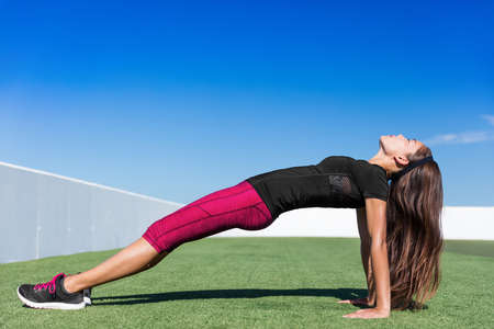 Yoga fitness woman stretching body in upward plank pose doing reverse planking exercise on outdoor grass park. Sport woman strength training her core body with bodyweight flexibility exercises. 免版税图像